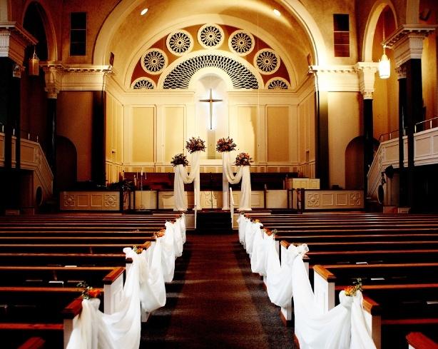 Białe wstęgi w alejce ślubnej jako dekoracja kościoła na ślub